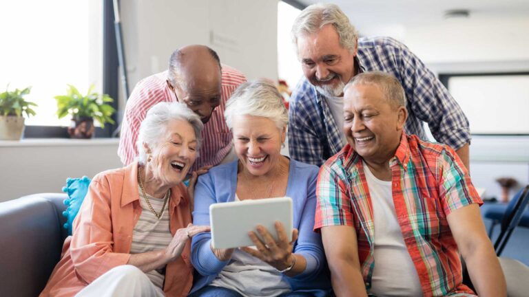 Cheerful senior friends looking at digital tablet