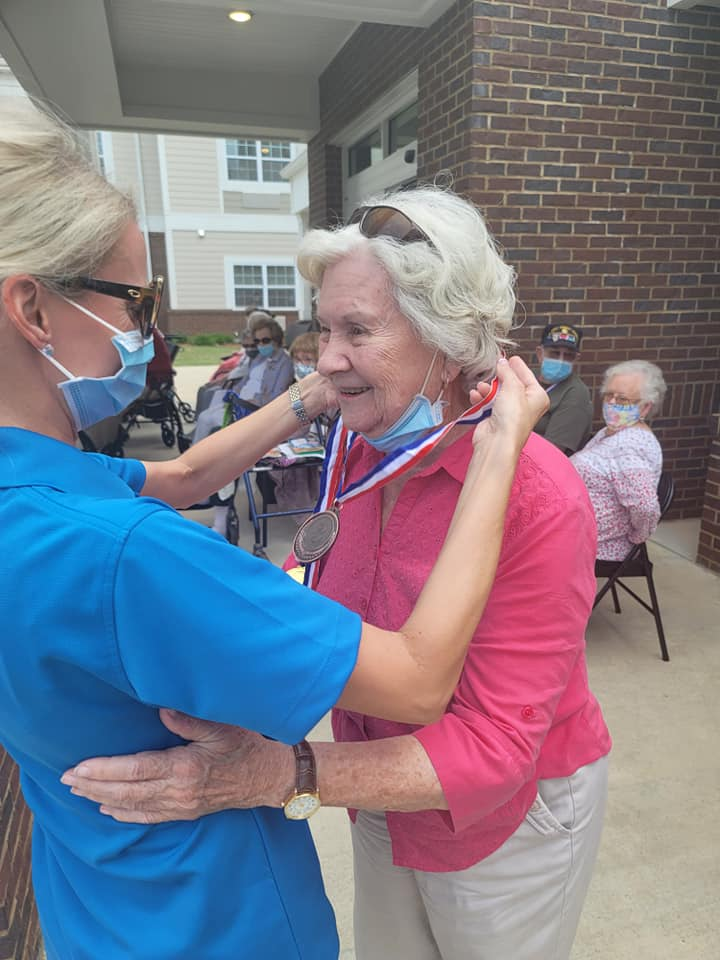 Woman receiving bronze metal after community-wide Olympic Games at Traditions of Athens