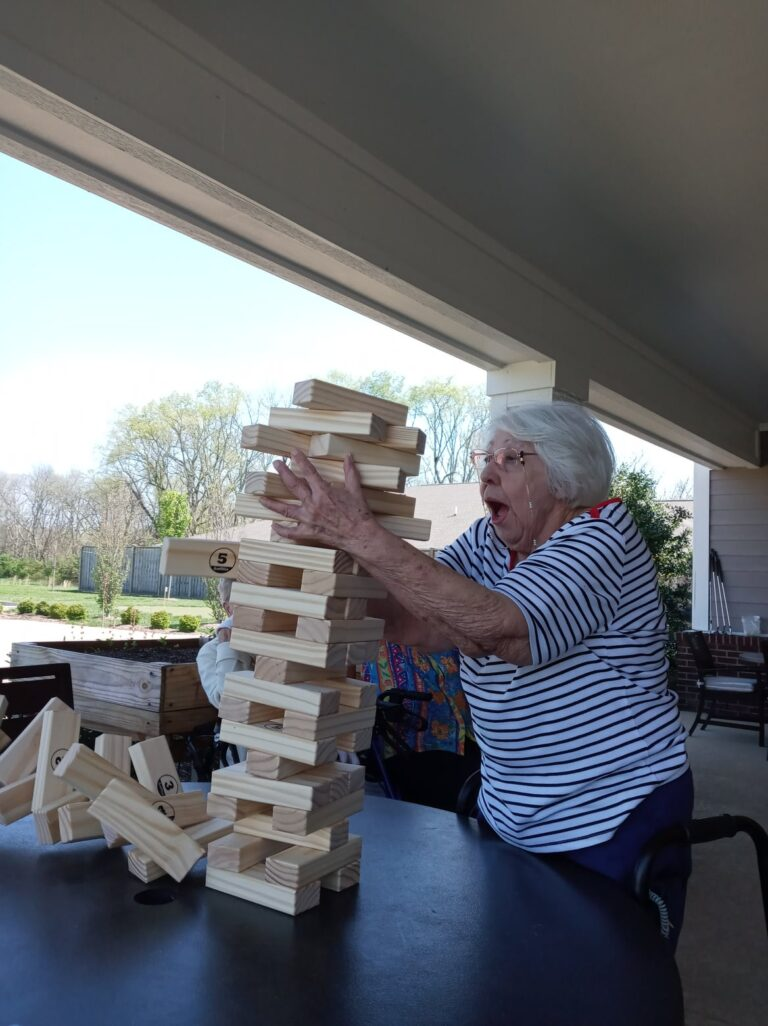 Giant Jenga blocks falling and woman trying to hold up at Traditions of Spring Hill