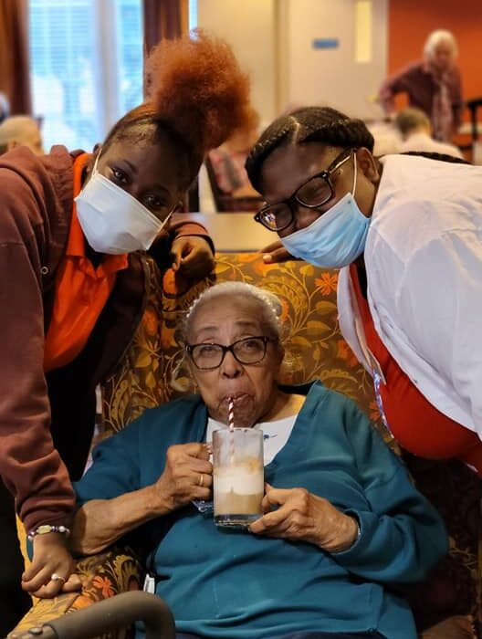 Group of women leaning in to take a picture with a milkshake at Vitality Living West End Richmond