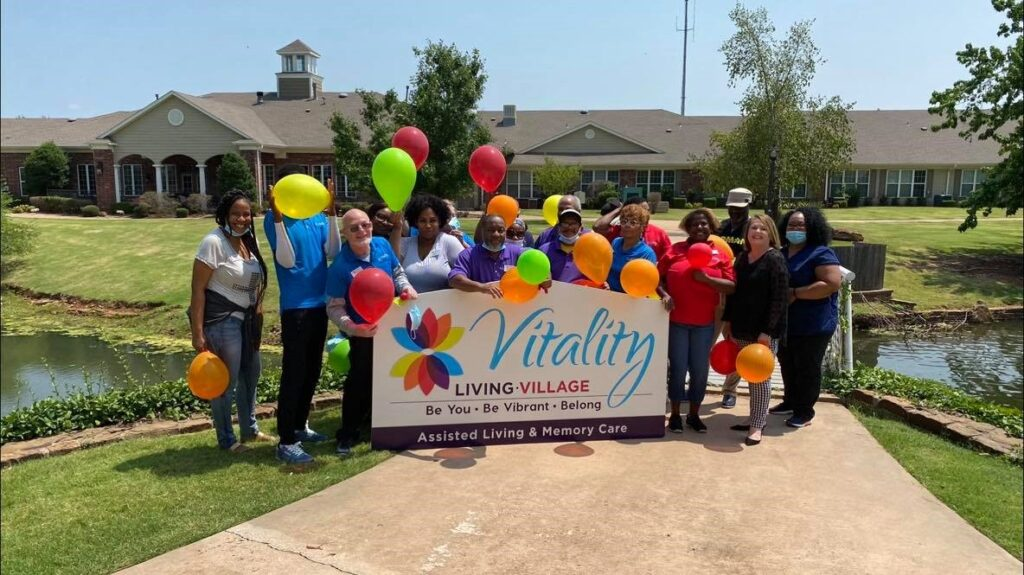 Group of people holding Vitality Living Village banner and balloons
