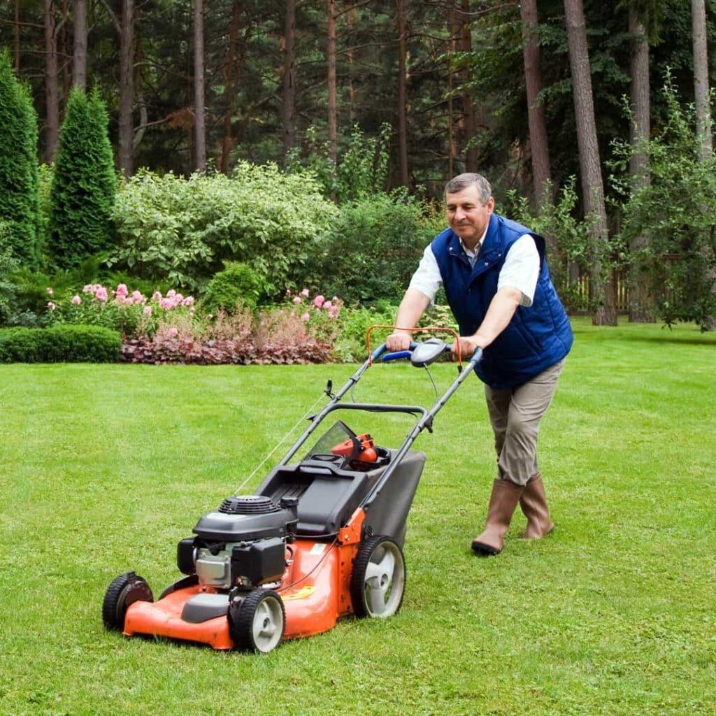 Senior man mowing the lawn