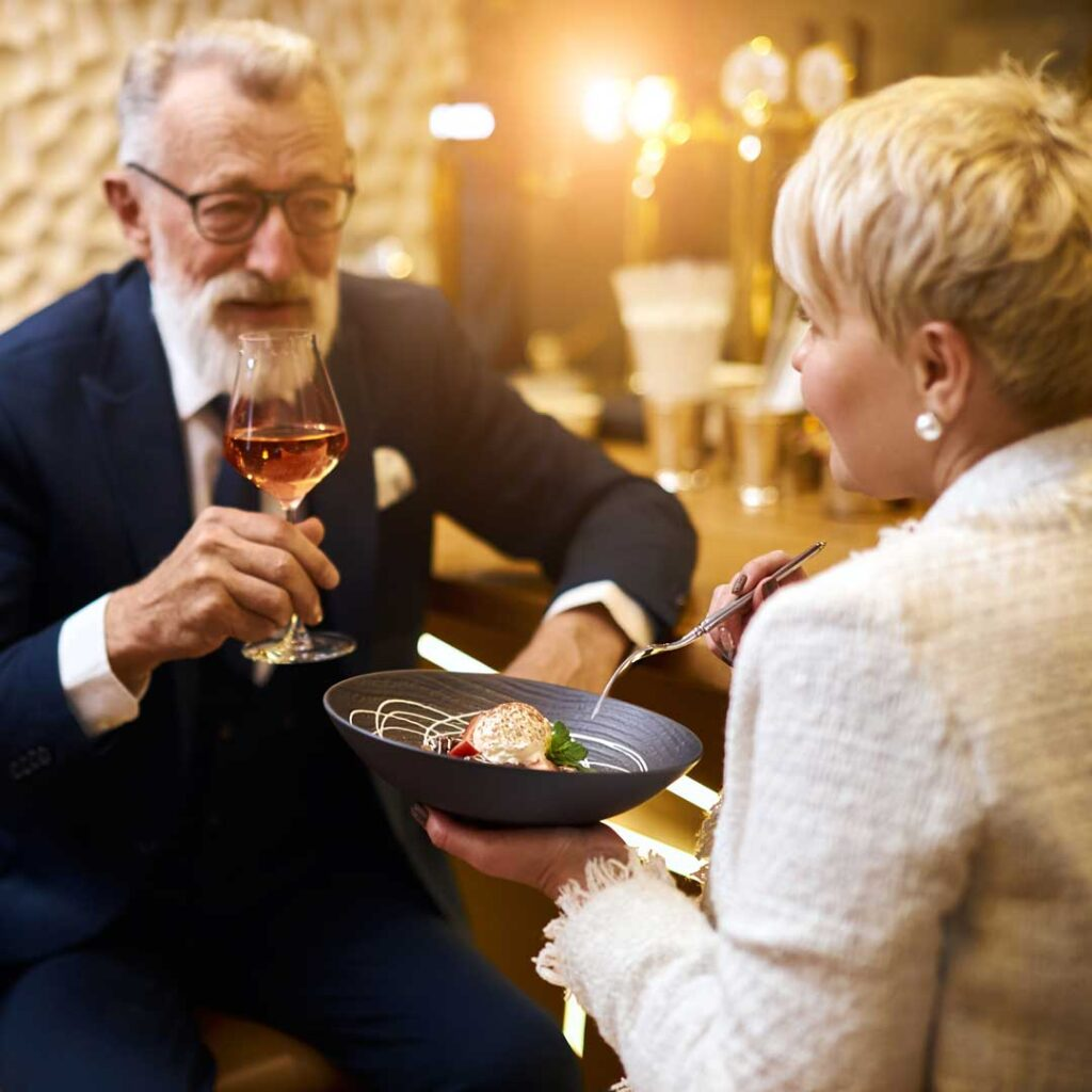 man and woman enjoying a dinner with an entre and glass of wine.
