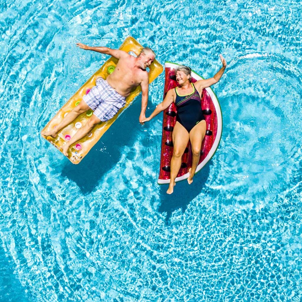 happy couple of old senior people enjoying the sun in the pool on floats