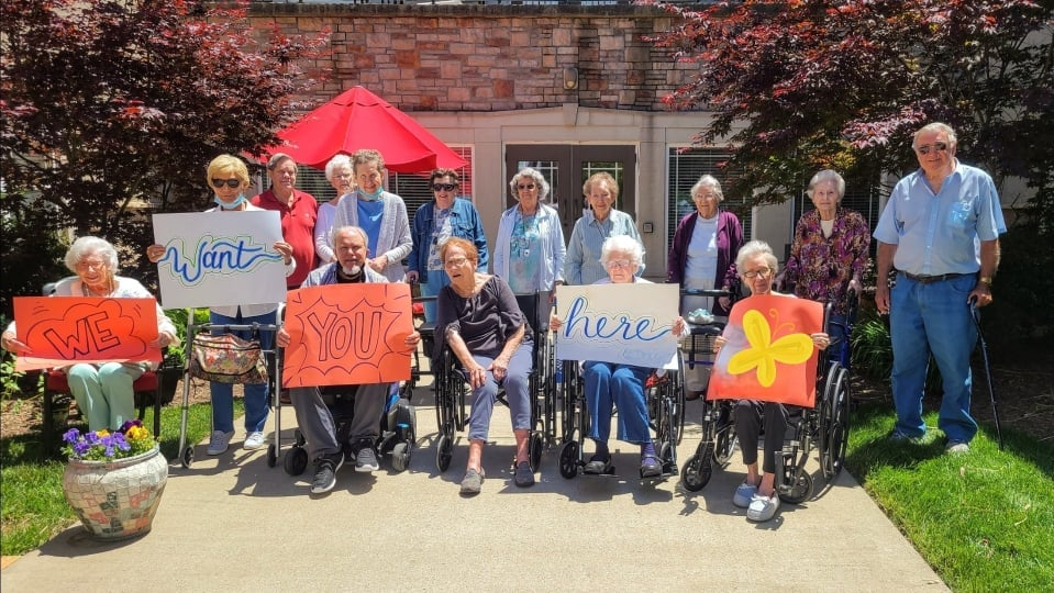 Group of Maristone residents holding welcome signs at Providence entrance
