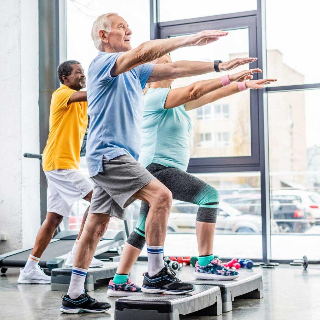 senior-athletes-synchronous-exercising-on-step-platforms-at-gy