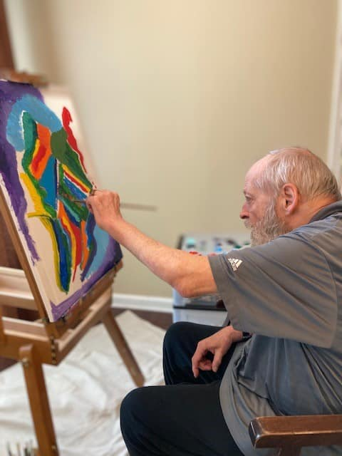 Man sitting and painting a canvas in vibrant colors at Vitality Living West End Richmond in Richmond, VA